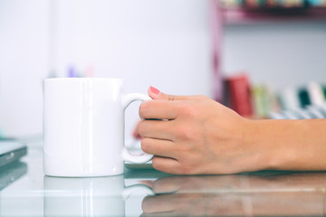 Woman Hand Holding a White Cup