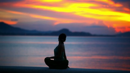 girl practicing yoga, doing twist on beautiful sunset