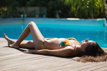 Slim brunette in bikini lying poolside