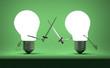 Glowing light bulbs fighting duel on green