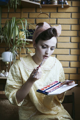 Beautiful vintage model portrait doing makeup