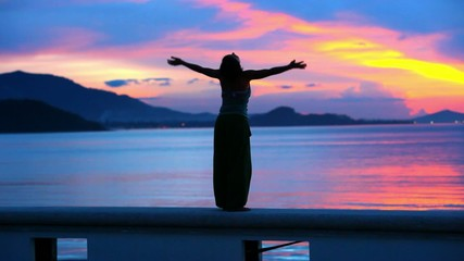 Beautiful sunset and young woman rising her hands into air.