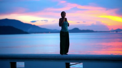 Happy woman admires the sunset on island Samui,