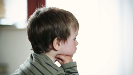 Little boy watching TV and sending kisses