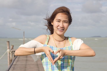 Beautiful girl make heart by hand
