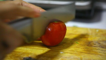 Female hands with knife, cutting fresh red tomato