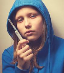 Dark portrait of a junk teen girl with syringe