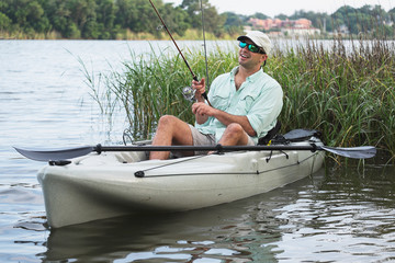 Man Fishing in Kayak in grassy waters