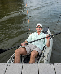 Relaxed Man Kicks Back in Fishing Kayak