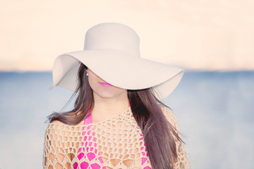 fashion beach woman with sunhat  covering one eye.