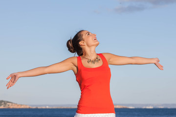 woman arms outstretched at beach