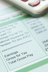Close Up Of Pay Slip With Calculator