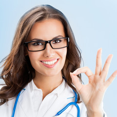 Doctor showing okay gesture, over blue