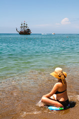 woman sitting on the sea beach and ship