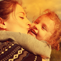 Bright closeup portrait of happy mother kissing daughter