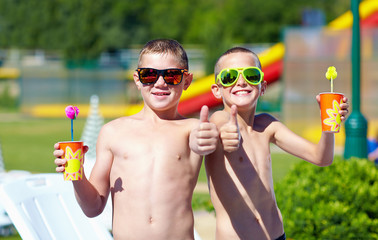 happy teenage boys showing thumbs up in aquapark