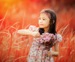 Asia little girl laughing in a meadow