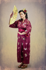 Woman standing in traditional national far eastern clothes with