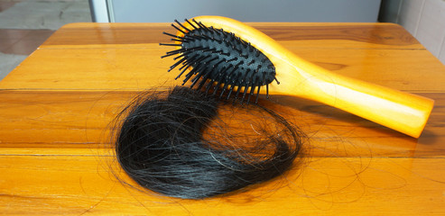 Brush with lost hair on wooden table