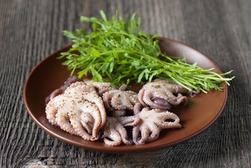 Octopus and green salad in a plate on the table