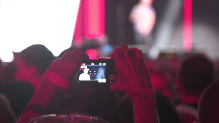 taking photo or recording video with camera at concert