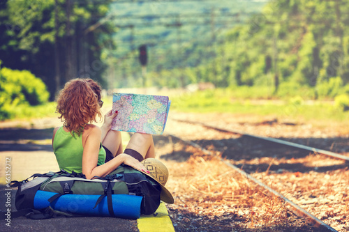 Girl wearing backpack holding map, waiting for a train. - 66352712
