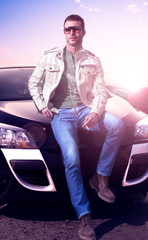 Young man portrait and car.Sunset landscape. Fashion lifestyle.