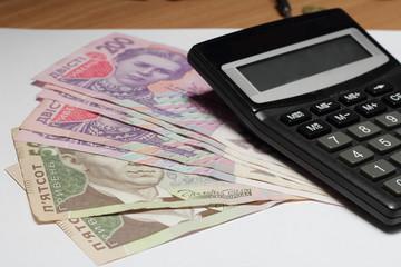 Ukrainian hryvnia and calculator on wooden table