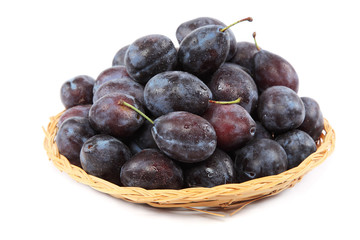 Fresh plums in a wooden basket.