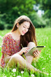 Woman sitting in meadow using digital tablet