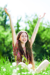 Woman with arms raised in meadow