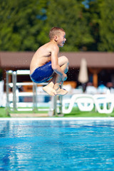 "excited teenage boy jumping ""bomb"" in the pool"