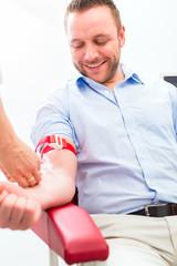 Ärztin bei Blutabnahme an Patient