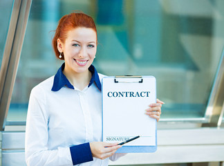 Portrait young businesswoman signing a contract