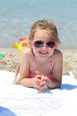 Bambina sulla spiaggia prende il sole