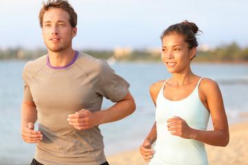 Running jogging couple training on summer beach