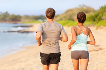 Jogging running couple on beach view from behind
