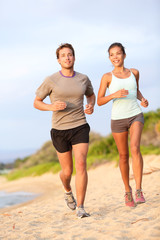 Running young couple jogging in beach sand happy