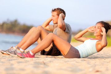 Situps on beach - young couple happy training