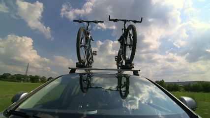 Car driving with two bicycles mounted on bike roof carrier