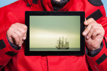 Man sailor showing cruise ship on tablet. Travel