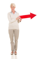 middle aged woman holding direction arrow