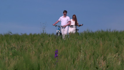 Young couple pushing bikes through the field