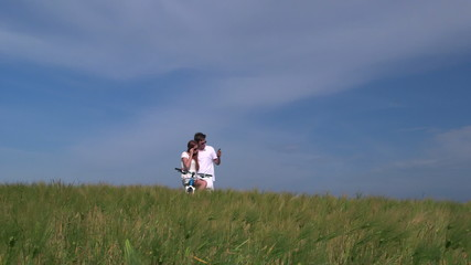 Young couple taking photo with smart phone in wheat field