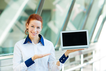 Portrait young business woman presenting, pointing at laptop