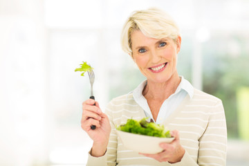 middle aged woman eating vegetable salad