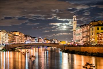 Pisa, Italy. City Lungarni illuminated with moonlight during ann