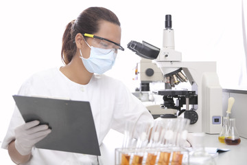 young female researcher holding papert in medical laboratory
