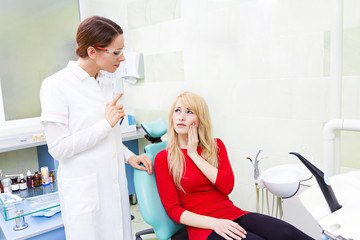 Woman patient in dentist office getting consultation from doctor