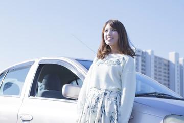 車にもたれて立つ女性